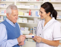 pharmacist showing an old man a box of medicine tablets